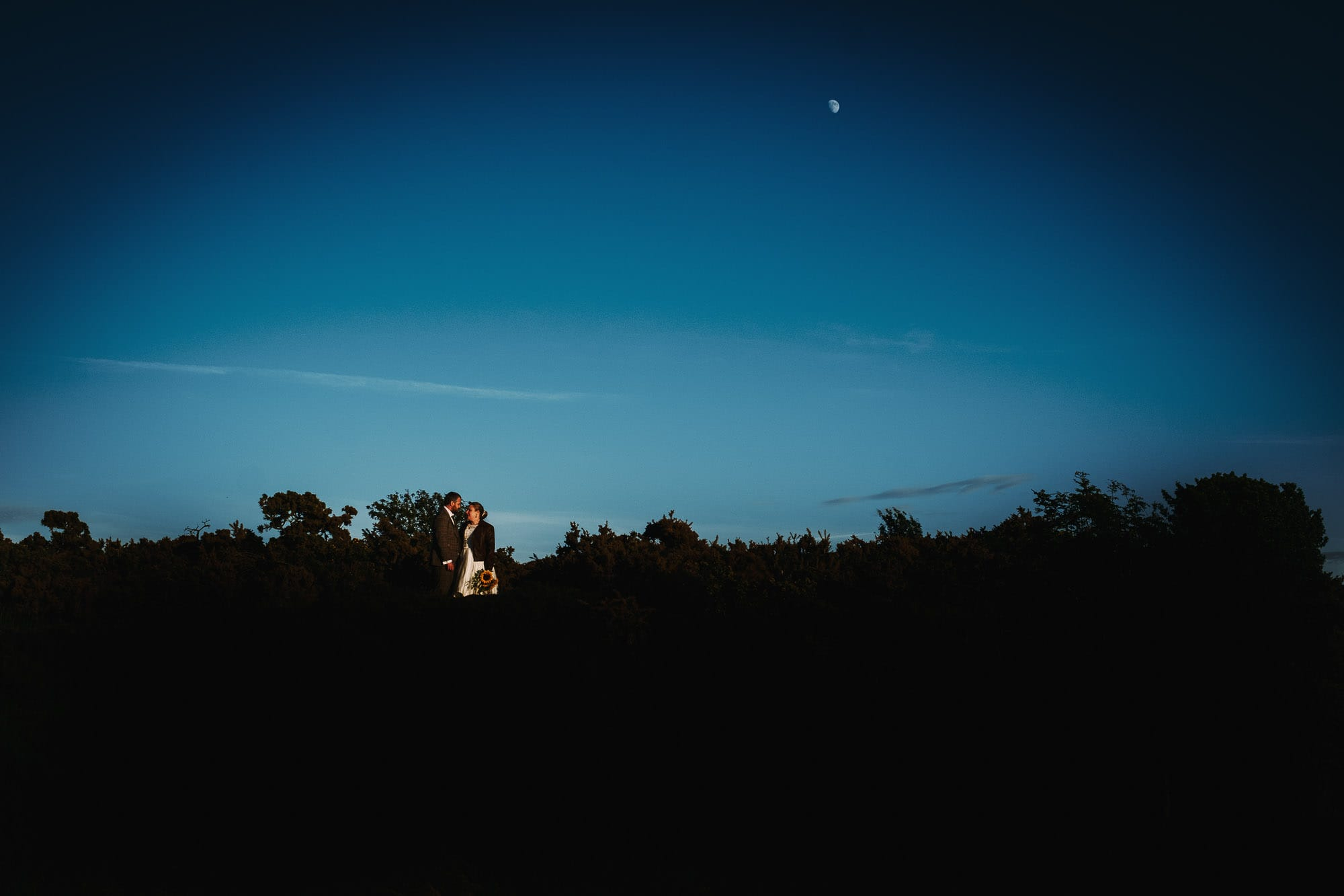 Scotland elopement Photographer captures bride and groom embracing with the moon behind them